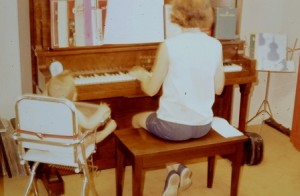 Me at the piano with appreciative baby sister as my audience (ca. 1970).